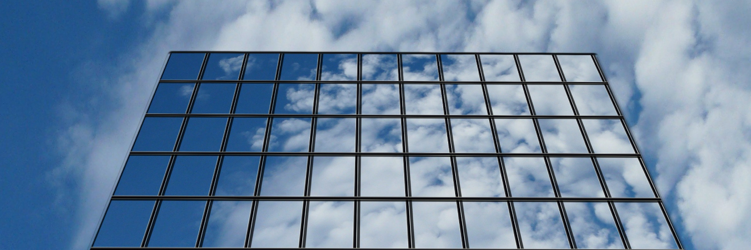 Building with clouds on mirrored windows