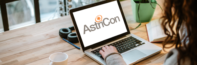 Open laptop on table with AstriCon logo virtual conference event
