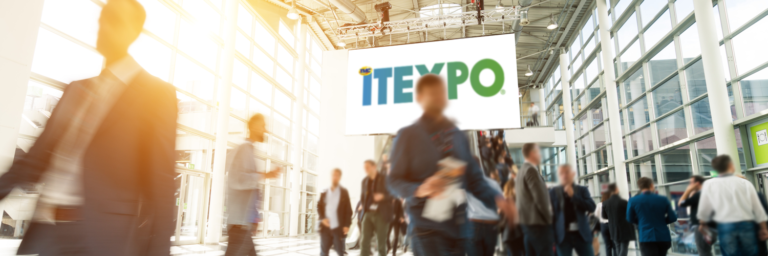 Trade show hall with people walking and ITEXPO sign above
