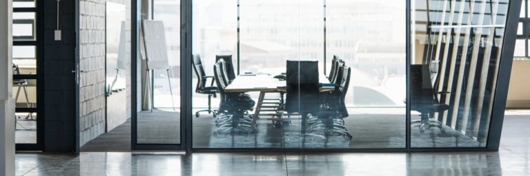 Empty conference room with glass walls and chairs