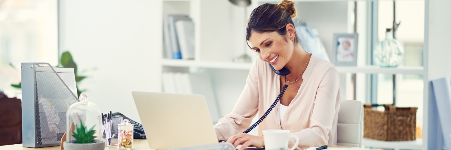 Woman working on laptop while on phone