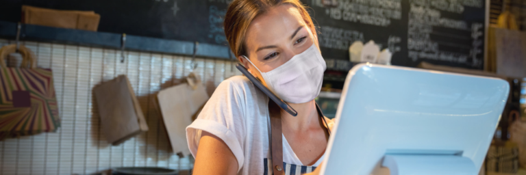 Woman wearing a mask taking a restaurant order on a cell phone
