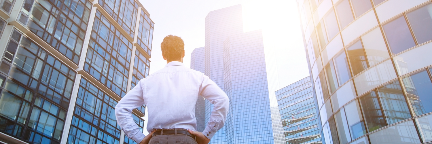 man standing in front of office buildings
