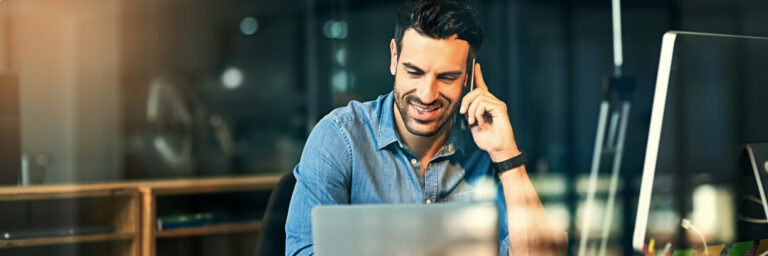 Man smiling, sitting at a desk in front of laptop with mobile phone up to his ear