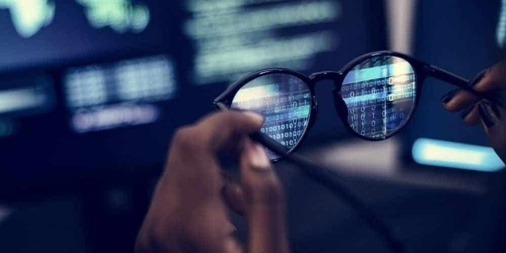 Person holding reading glasses in front of computer screen