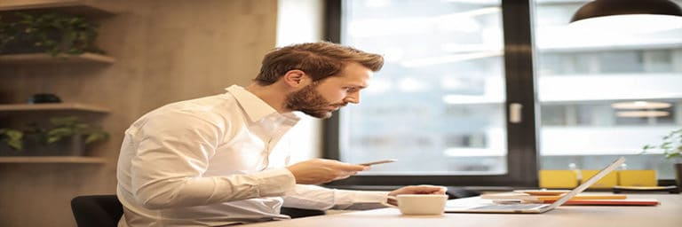 man using phone at desk with laptop