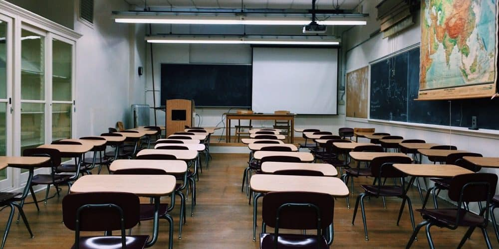 classroom with desks, chalkboard, and map