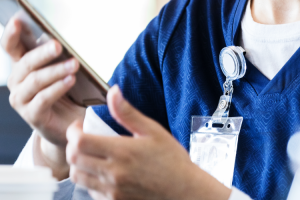 Essential worker using mobile device to alert patient that their appointment is ready.